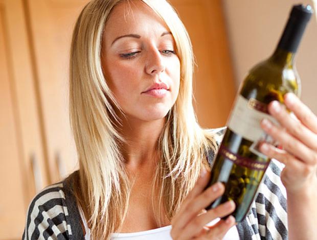женщина смотрит на бутылку