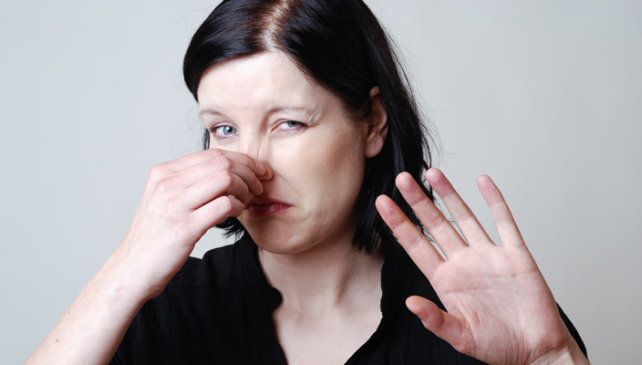 женщина морщится от плохого запаха