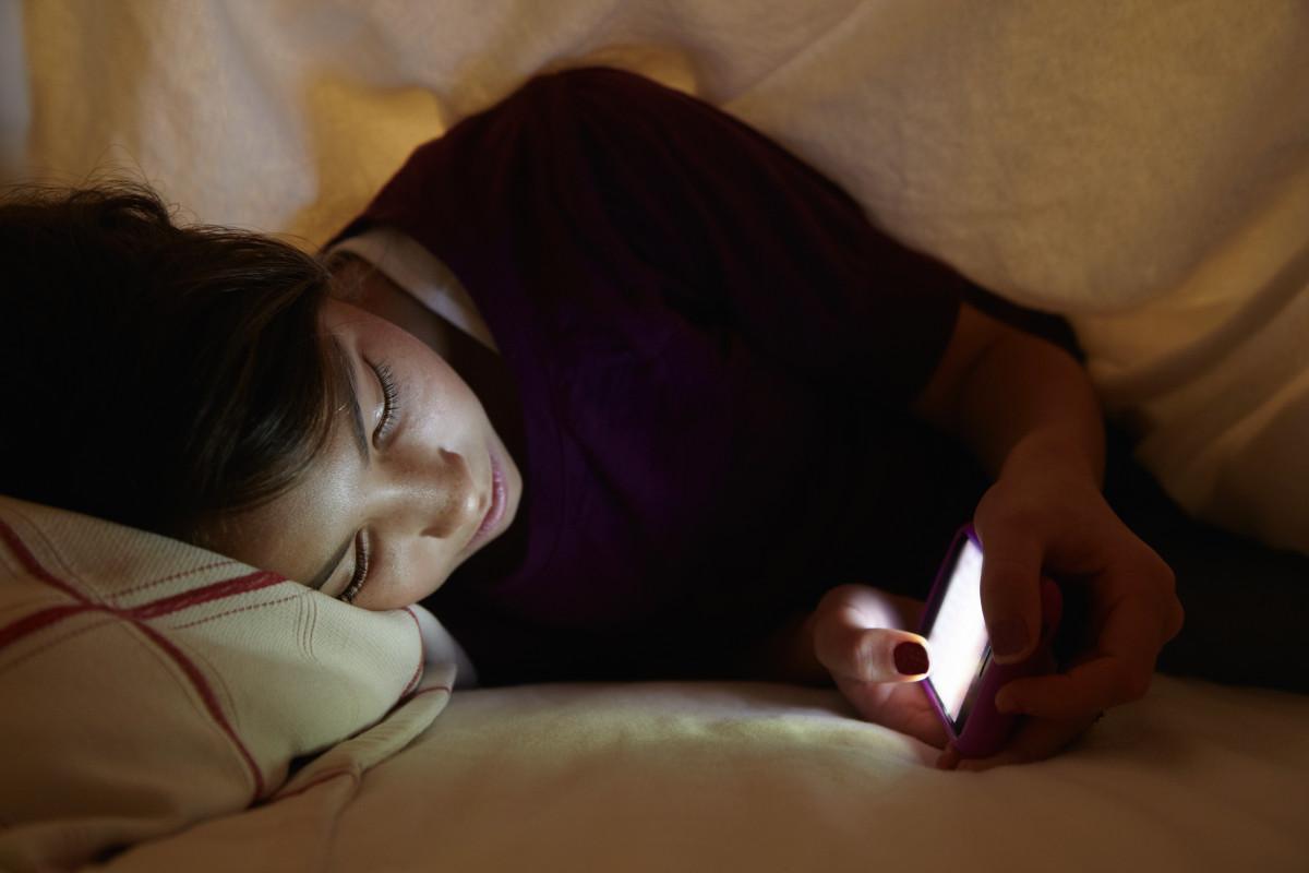 девушка лежит с телефоном