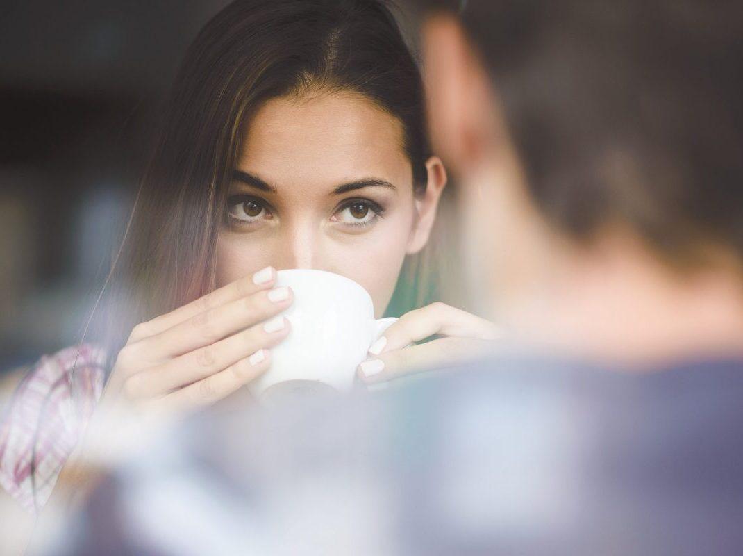 девушка пьет кофе и смотрит на парня