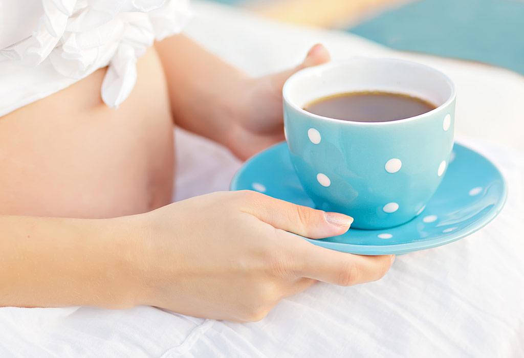 беременная держит чашку