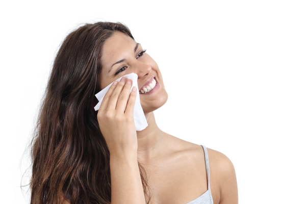 женщина протирает лицо салфеткой