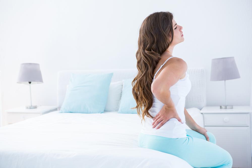 женщина сидит на кровати болит спина поясница