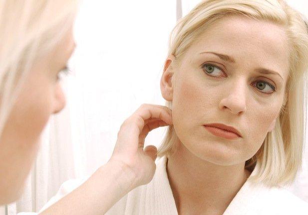женщина смотрит в зеркало на свои щеки