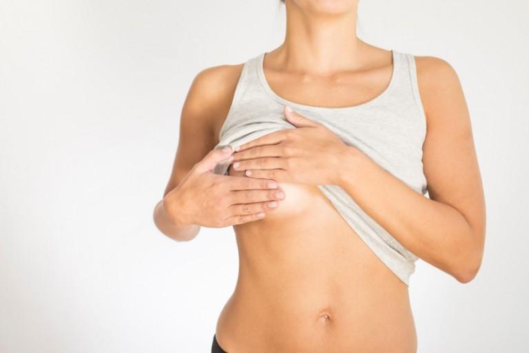 женщина в майке прикрывает грудь