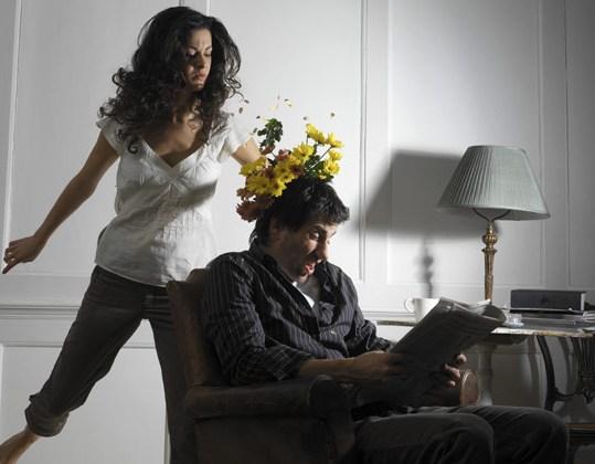 женщина бросает в читающего мужа букетом
