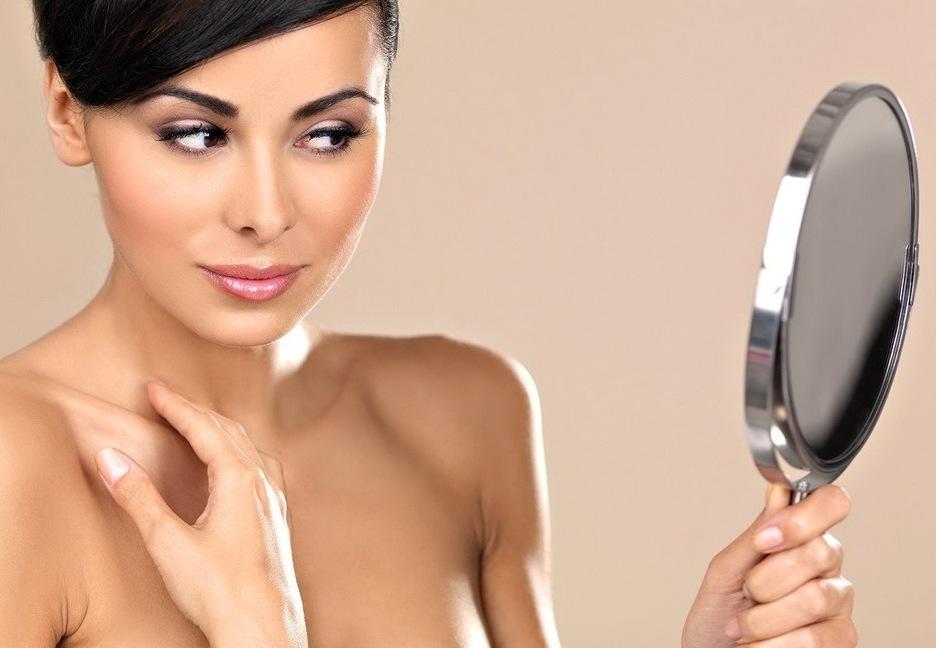 женщина с красивыми бровями смотрит в зеркало