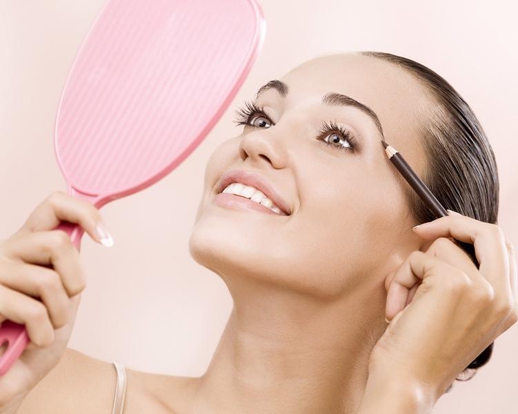 девушка с зеркалом красит брови