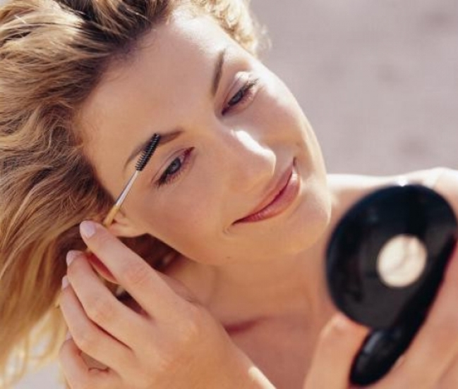 женщина расчесывает брови у зеркальца